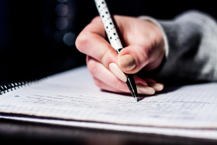 kobieta robiąca notatki - informatyka studia WSZIB