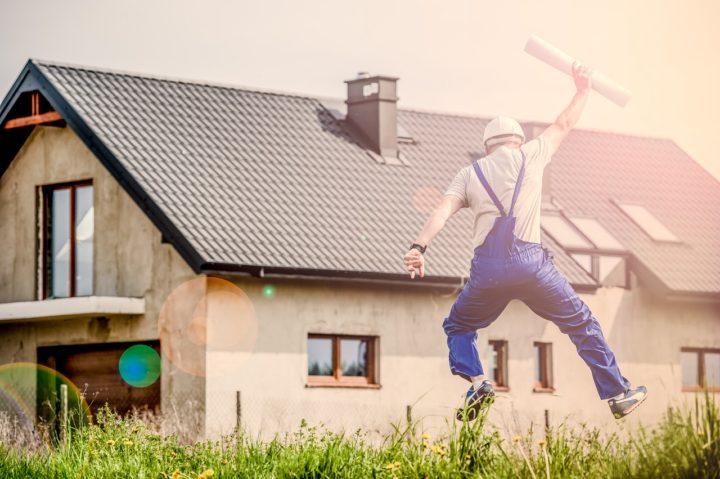 Budowlaniec okazujący radość przed wybudowanym domem