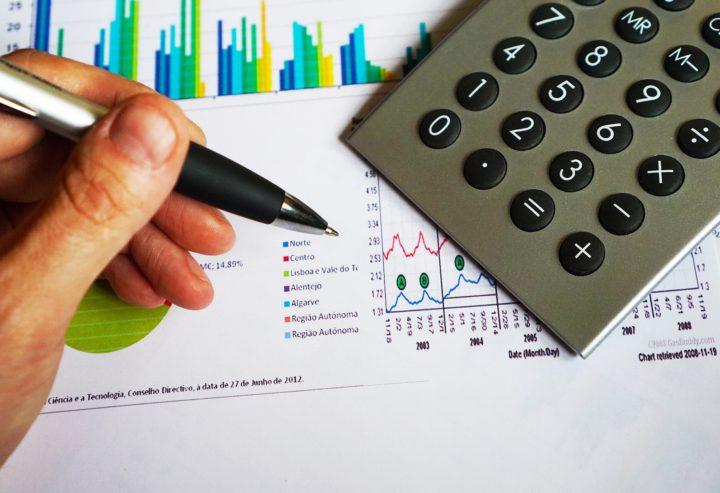 dłoń trzymająca długopis na tle kalkulatora i wykresów