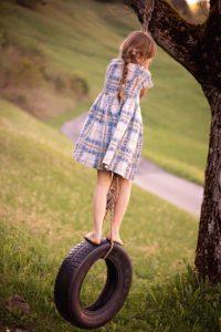 Dziewczynka, która lubi huśtawki ogrodowe dla dzieci
