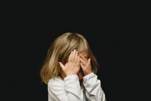 dziecko zakrywa twarz